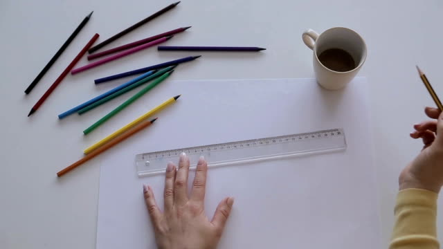 The female architects are using a ruler in the office table,close up