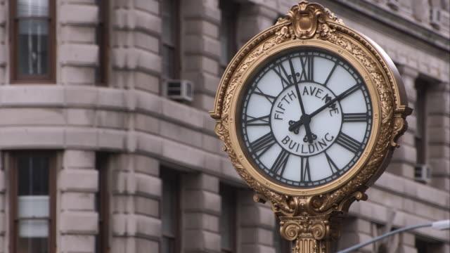 the fifth avenue building clock in manhattan - römische zahl stock-videos und b-roll-filmmaterial