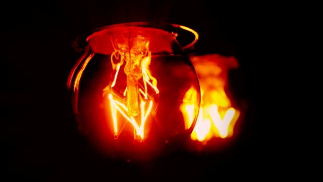 vídeos de stock, filmes e b-roll de the filaments inside light bulbs flicker. - filamento