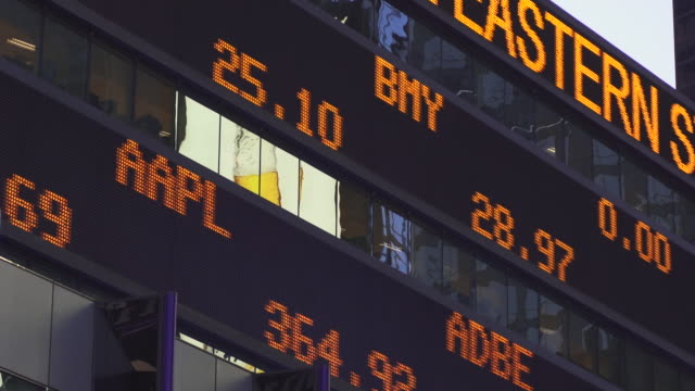the financial ticker sign in time square at dusk - stock market stock videos & royalty-free footage