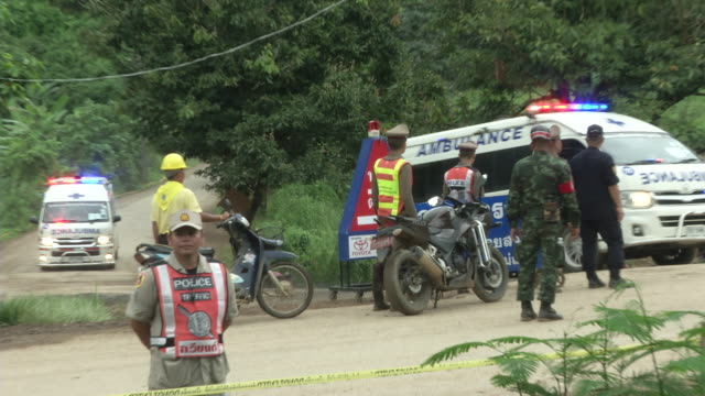 the first ambulance leaves the tham luang cave area after divers evacuated some of the boys among a group of 13 trapped in a flooded cave in khun nam... - thai culture stock videos & royalty-free footage