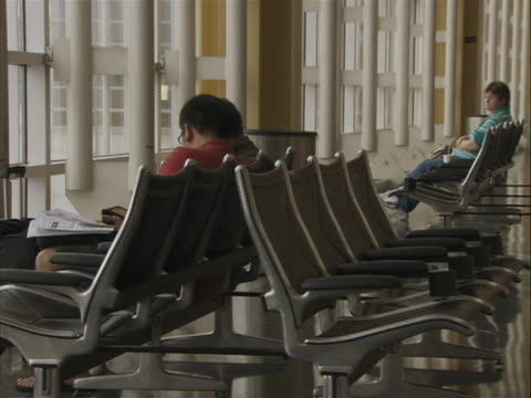 the first shot is a mcu of people sitting in the waiting area of ronald reagan washington airport. there are two rows of seats with two people with... - flughafen washington ronald reagan national stock-videos und b-roll-filmmaterial