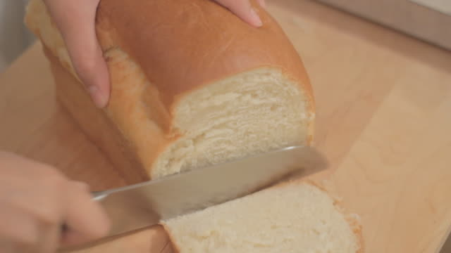 the first slices on a fresh loaf of bread, from raised side view. - white bread stock videos and b-roll footage