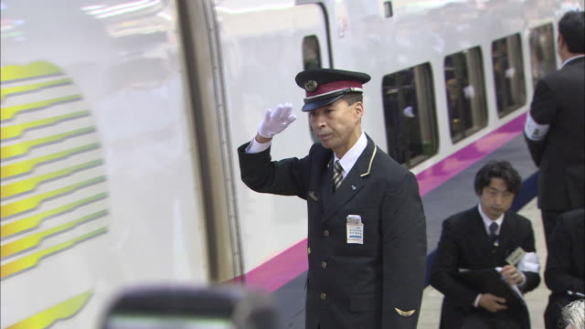 the first train at tokyo station, hayate no.11, departs as train conductors salute. - train guard stock videos & royalty-free footage