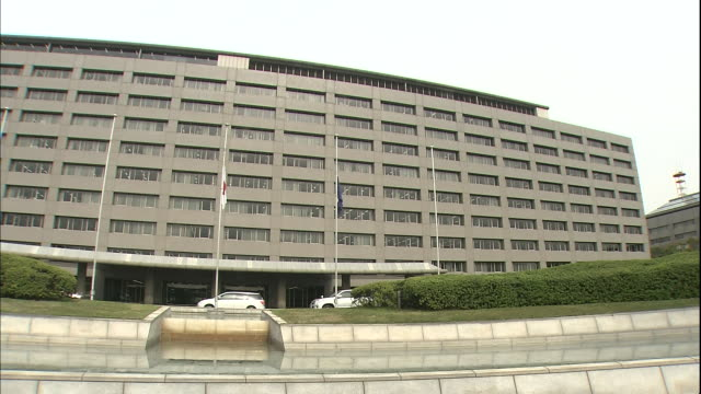 the flag of fukuoka hangs at half-mast in front of the fukuoka prefectural government building in japan. - japan flag stock videos & royalty-free footage
