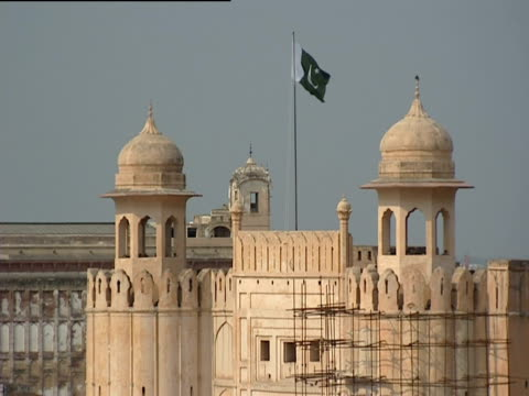 the flag of pakistan waves above the lahore fort, pakistan. - lahore pakistan stock-videos und b-roll-filmmaterial
