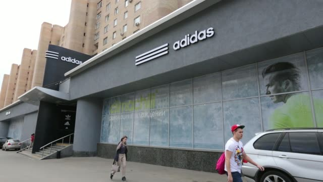 The flag of the Russian Federation right hangs alongside a flag of St George outside the Adidas AG sportswear store in Moscow Russia on Friday May 2...