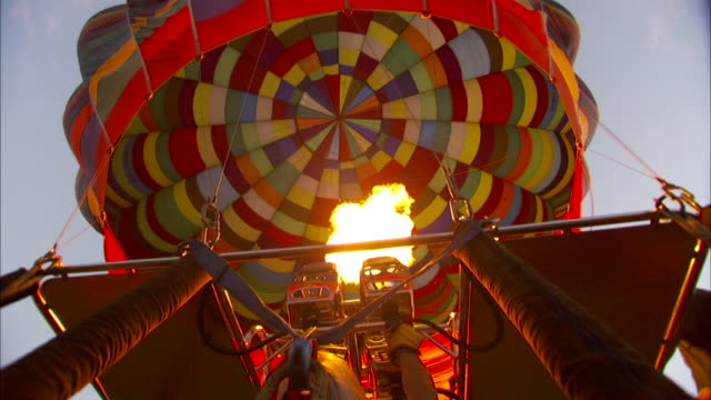 vídeos de stock e filmes b-roll de the flame from a burner sends hot air into the envelope of a hot air balloon. available in hd - soprar