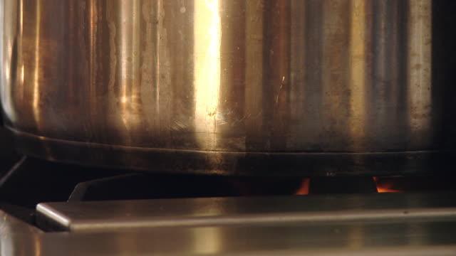 The flame of a gas stove heats a aluminum cauldron