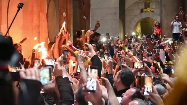 vídeos de stock e filmes b-roll de the flame pours forth from the tomb lighting up the cavernous church as fire passes from candle to candle held by thousands of christian pilgrims... - milagres