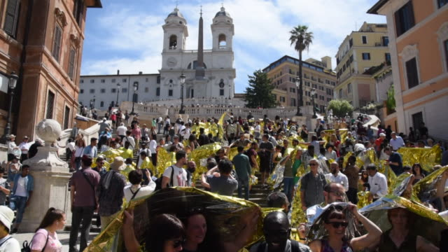 the flash mob of the protesters including a large group of migrants wrapped in golden thermal blankets in the spanish steps of 42 ngos for the launch... - flash mob stock videos and b-roll footage