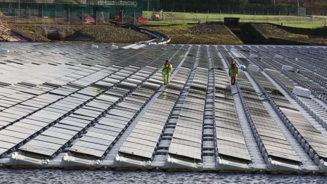 the floating solar farm being grid connected on godley reservoir in hyde manchester uk the scheme is a 3 mw system comprising of 10000 photo voltaic... - grid stock videos & royalty-free footage