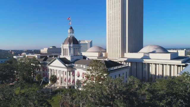 the florida state capitol, tallahassee.  aerial drone video with the ascending and tilting down complex cinematic camera motion. - government building stock videos and b-roll footage