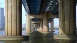 The flow of the river under the bridge.