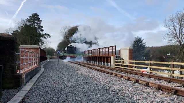the flying scotsman breaks a banner as it crosses the newly renovated butts bridge in alton, hampshire, to officially re-open the mid hants railway's... - alan titchmarsh stock videos & royalty-free footage