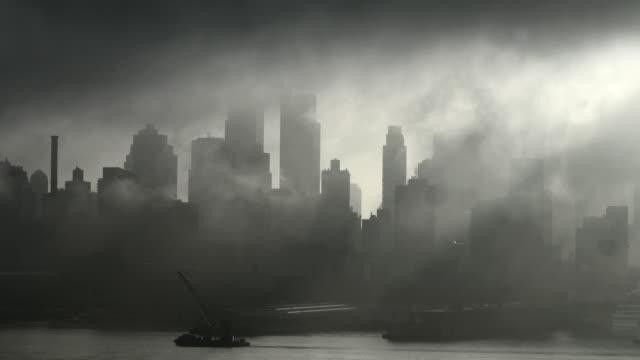 The fog slowly lifts over a dark and grey Manhattan Skyline