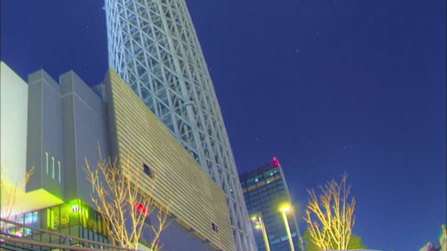 the foot of tokyo sky tree: tilt up; the orbit of the stars and upper part of tokyo sky tree: time lapse.  - low angle view stock-videos und b-roll-filmmaterial