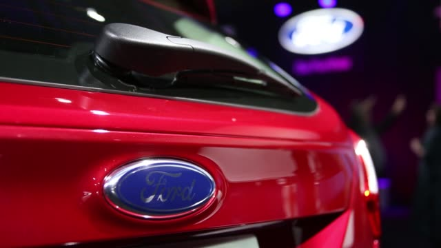 cs the ford motor co logo is seen at a media event cs pull focus into ford logo ws attendees gather around a ford motor co focus vehicle on display... - ford motor company stock videos & royalty-free footage