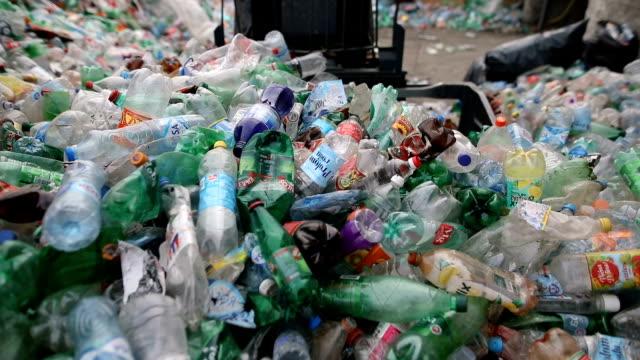 vídeos de stock, filmes e b-roll de a empilhadeira coloca garrafas plásticas embaladas em uma pilha. trabalhando em uma fábrica de reciclagem - coleção