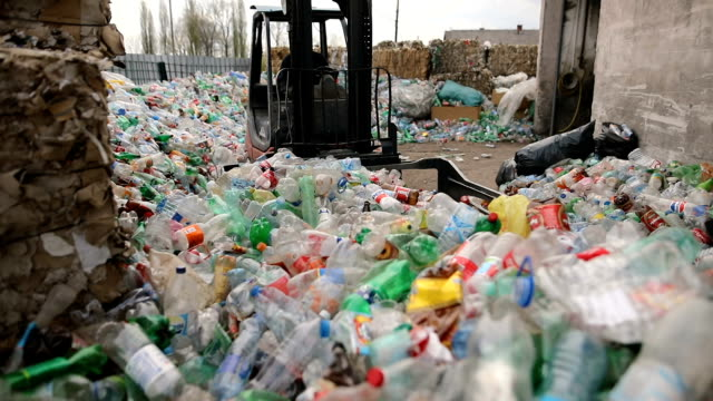 フォークリフトはプラスチックボトルを積み重ねて置いています。リサイクル工場で働く - リサイクル工場点の映像素材/bロール