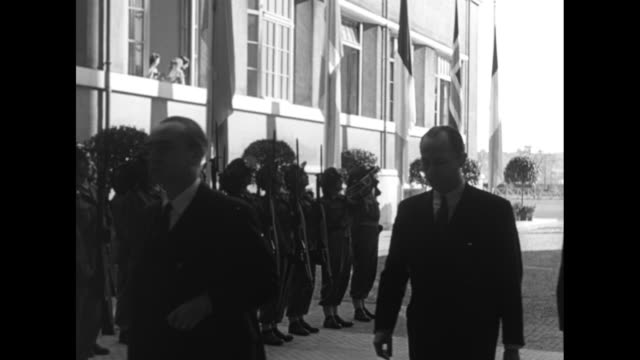 EXT the Foro Italico in Rome site of North Atlantic Council meeting / [dark shots] VS Italian honor guard stands in background as various delegates...