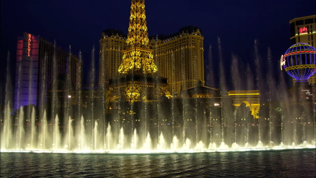 the fountains of the bellagio hotel in las vegas create an impressive water show. - las vegas replica eiffel tower stock videos & royalty-free footage