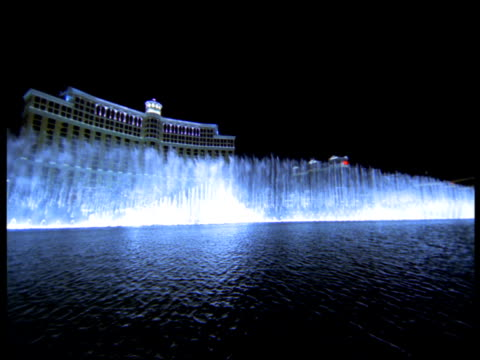 the fountains of the bellagio perform at night in front of the bellagio hotel and casino. - 2001 stock-videos und b-roll-filmmaterial