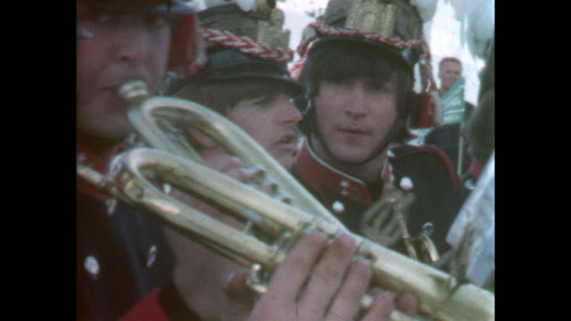 The four Beatles in traditional brass band uniforms playing trumpets goofing around and making faces / 8mm amateur home movie footage filmed by the...