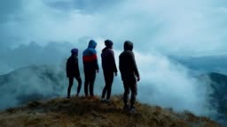 The four people standing on a picturesque mountain