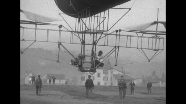 the frame of a prototype helicopter suspended from a balloon with twin propellers rises precariously in the air with amusing footage of men running... - invention stock videos & royalty-free footage