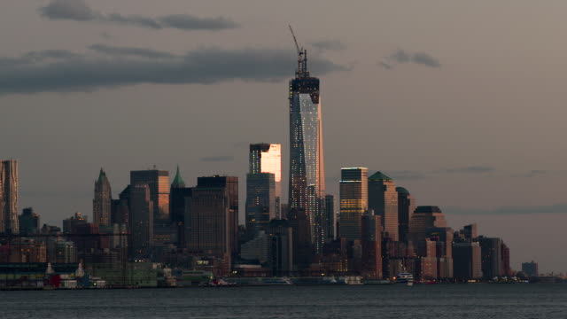 the freedom tower is being built in lower manhattan the skyline the warm glow of twilight fills the sky. - one world trade center stock-videos und b-roll-filmmaterial