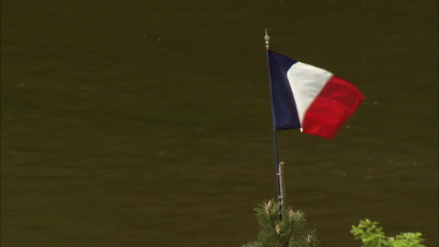 The French flag flies near a river. Available in HD