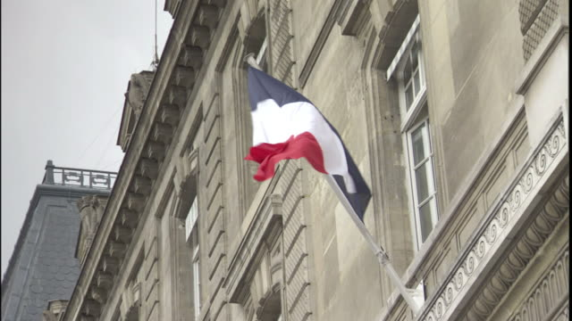 The French flag waves above the entrance of a government building in Paris.