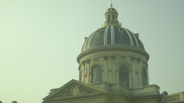 The French national Tricoleur flag stands on a pole outside the dome of the prestigious Institut de France, Monnaie (6th arrondissement), Paris, France.
