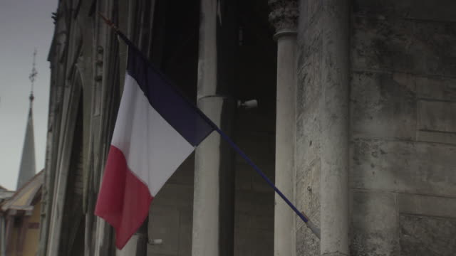The French Tricolore flag hangs from a flagpole on a building in Troyes, France.