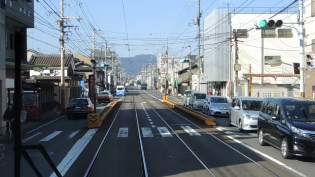 the front view of electric trams, electric trams in kyoto city - tram stock videos & royalty-free footage