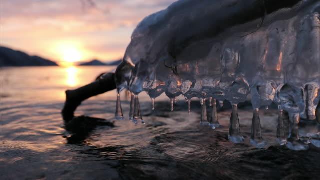 vídeos de stock, filmes e b-roll de the frozen spray on the lakeshore and close-up shot of frozen spray glistening in the sun,hokkaido,japan - pingente de gelo