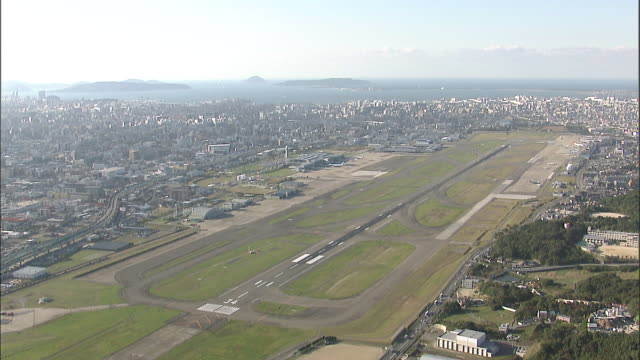 the fukuoka airport runway cuts through the middle of fukuoka city, japan. - fukuoka prefecture stock videos & royalty-free footage