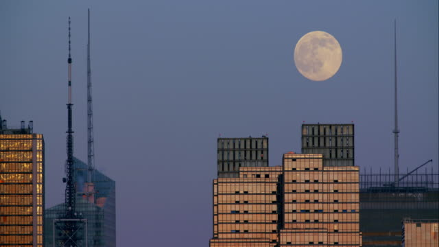 the full moon rises in-between the midtown manhattan skyscrapers. - bank of america stock videos and b-roll footage