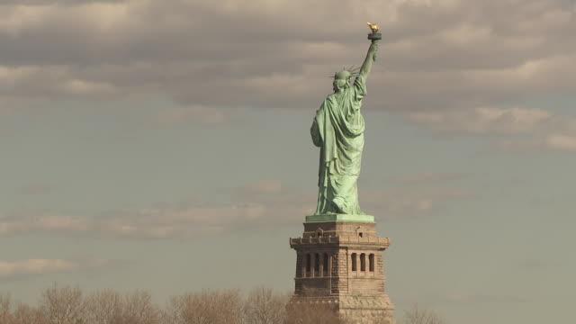 vídeos de stock, filmes e b-roll de the full profile of the back side of the statue of liberty. - estátua