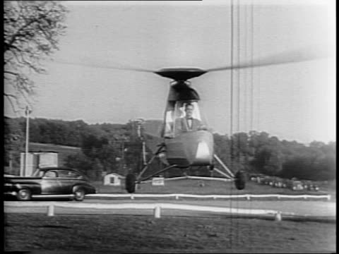 the future of transportation the helicar was invented by frank n piasecki / piasecki comes down steps of house and climbs into helicopter / view from... - 発明家点の映像素材/bロール
