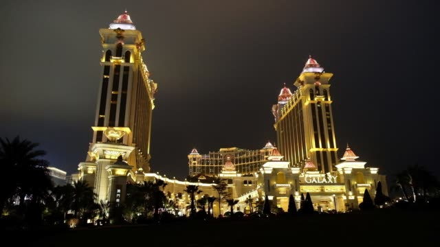 The Galaxy Macau casino and hotel developed by Galaxy Entertainment Group Ltd stands illuminated at night in Macau China on Saturday Feb 24 Signage...