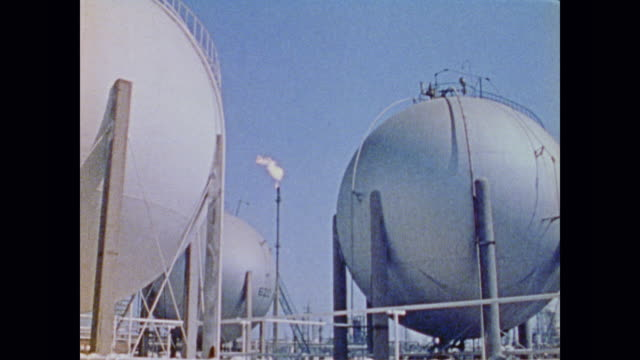 vidéos et rushes de the gas flare of a refinery sits at the center of storage tanks and various pipes - industrie du pétrole