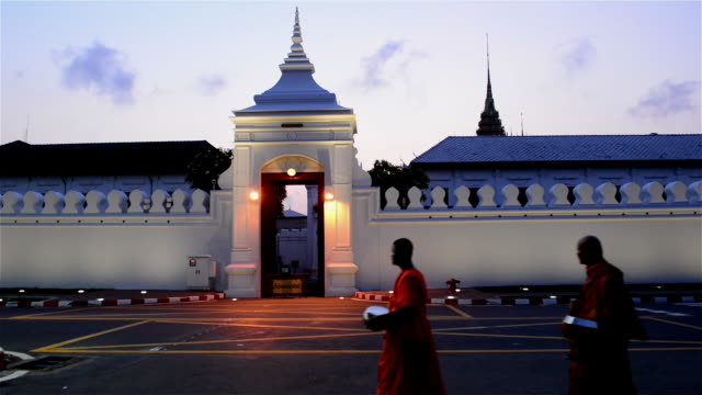 the gate of bangkok grand palace with monks walking pass - alm stock-videos und b-roll-filmmaterial