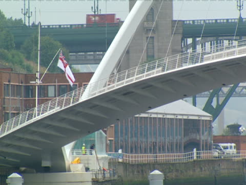 the gateshead millennium bridge arches over  the river tyne in gateshead-newcastle, england. - newcastle upon tyne stock videos & royalty-free footage