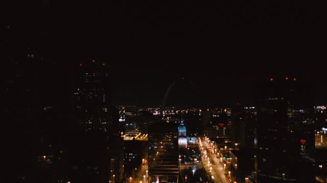 the gateway arch dimly shines behind the bright city lights of st. louis, missouri at night. - jefferson national expansion memorial park stock videos & royalty-free footage