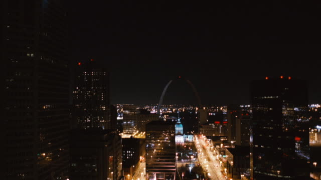 vídeos de stock e filmes b-roll de the gateway arch faintly glows behind the bright city lights of st. louis, missouri at night. - jefferson national expansion memorial park