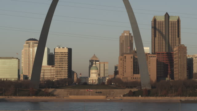 The Gateway Arch rises above skyscrapers and a courthouse.