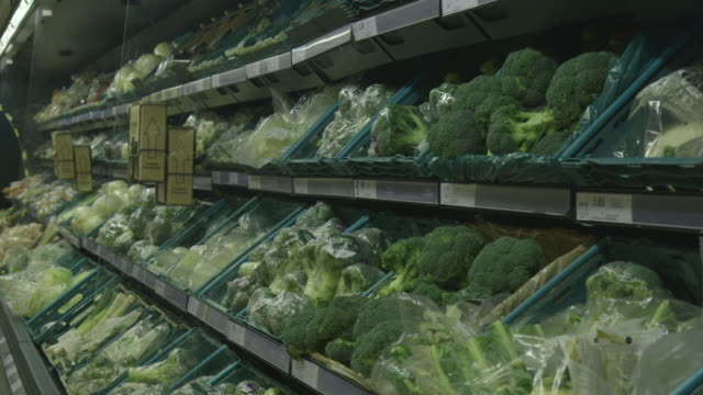 vídeos y material grabado en eventos de stock de the gentle breeze of a large refrigerator disturbs the plastic wrapping of green vegetables on display at a uk supermarket. - embalaje