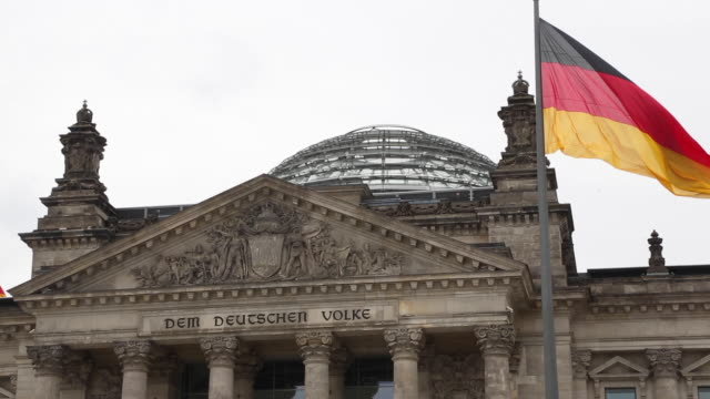 the german flag flies atop the usuallybusy reichstag seat of the german parliament the bundestag as few tourists visit the site due to the global... - palazzo del parlamento video stock e b–roll